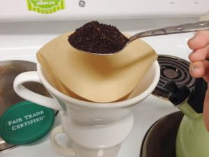 Place the paper filter inside the ceramic filter & add 2 heaping scoops of coffee.