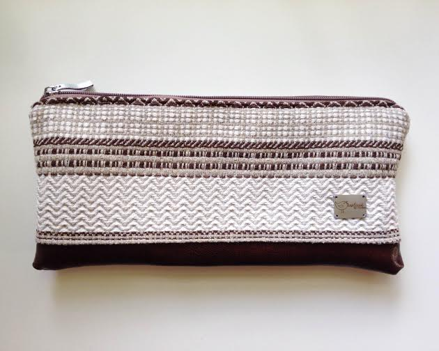 Brown patterned zip-top clutch with vegan leather bottom.